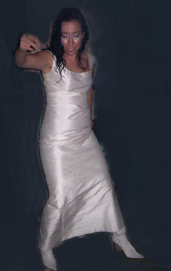 """Ώπα! Από το πάρτυ του γάμου, με φωτογράφο την CosmoΡούλα. Δεν είναι η πλέον κολακευτική πόζα για να αναδειχθούν οι γραμμές του νυφικού, όμως μπορείτε να πάρετε μια ιδέα. Στην εικόνα προσθέτετε και δαντέλα σε ρόλο πέπλου, την οποία φορούσα κατά τη διάρκεια του μυστηρίου -ναι, μπότες είναι αυτές που βλέπετε στα πόδια μου. Όταν τις είδα, μου """"μίλησαν"""". Τις αγόρασα χωρίς δεύτερη σκέψη και η συγκυρία δικαίωσε την επιλογή: την ημέρα του γάμου έβρεχε… © beautyworkshop.gr"""