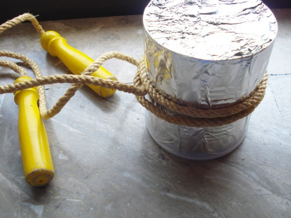 Τυλίγουμε την κονσέρβα με το αλουμινόχαρτο (ανάμεσα, απλώνουμε και λίγη κόλλα, για σταθερότητα). Στη συνέχεια, τυλίγουμε το σχοινάκι 1 ή 2 φορές, ανάλογα με το πόσο ψηλό είναι το παιδί, φροντίζοντας ώστε οι δύο άκρες να έχουν ίσες αποστάσεις. Όταν το τουμπανάκι τελειώσει, τα σχοινιά περνούν από το πίσω μέρος του λαιμού, το τουμπανάκι σταθεροποιείται μπροστά στο στήθος του παιδιού, και με τα χέρια ελεύθερα, χρησιμποιεί τα 2 ξύλινα μέρη ως μπαγκέτες. © beautyworkshop.gr